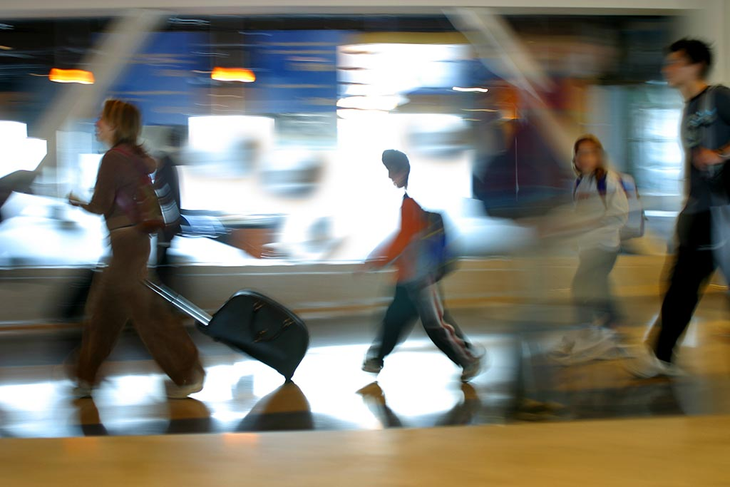 Blurred image of people with suitcases walking in the airport