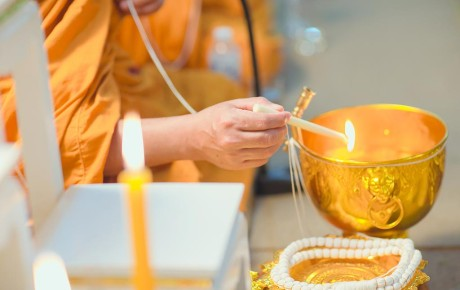 Monk lighting a candle in ceremony