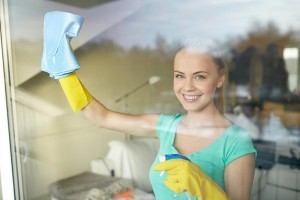 Woman wearing gloves cleaning a window