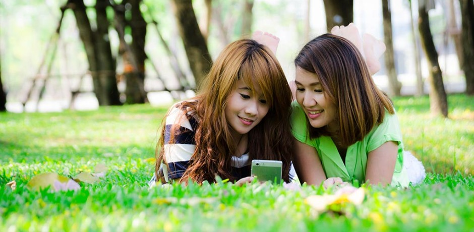 Two young Asian women lying down in the park looking at a mobile phone