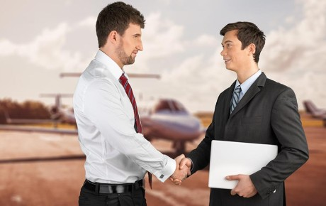 Businessmen shaking hands with aeroplane in the background
