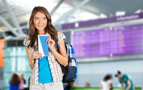 Young girl holding travel document in airport