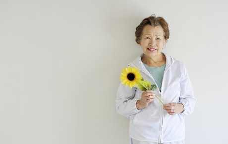 Older Asian lady holding a sunflower