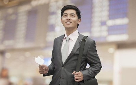Young Asian businessman holding air ticket at airport