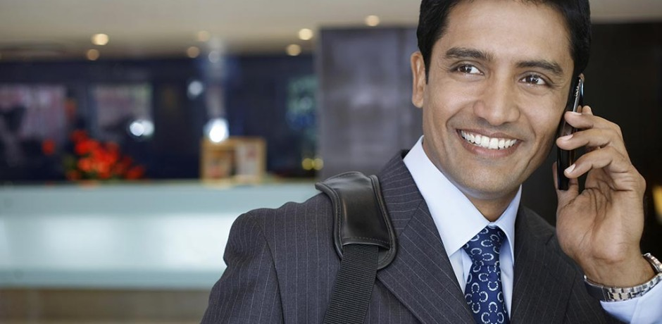Smiling Indian businessman on his mobile phone