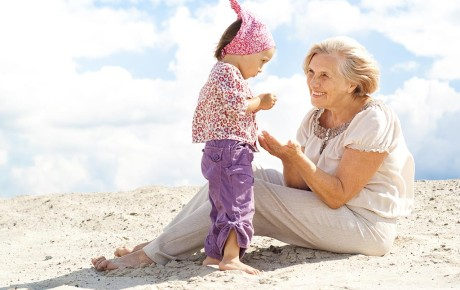 An elderly lady with a young child on a beach